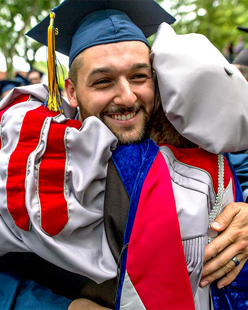 A graduate hugging a professor after the commencement ceremony.