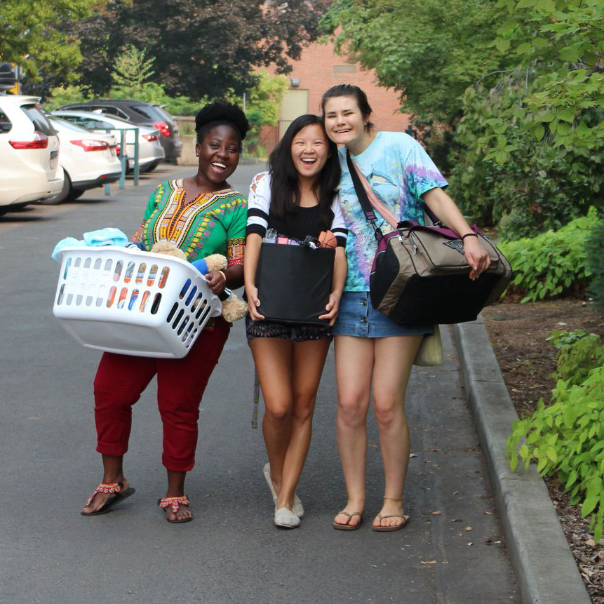 Three students smile at the camera while moving their belongings into their residence hall.